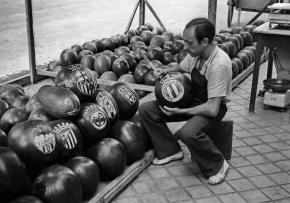 Un frutero talla escudos de equipos de fútbol en unas sandías. Madrid, 1951